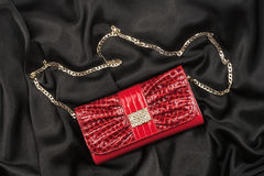 Red lacquer bag lying on a black silk Stock Images