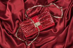 Red lacquer bag lying on a red silk Royalty Free Stock Images