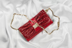 Red lacquer bag lying on a white silk Stock Image