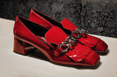 Red lacquer women shoes. Prada Red women lacquer shoes with chain and tassels the heels height is low to medium ... the shoes are beautiful glossy high-fashion stock images