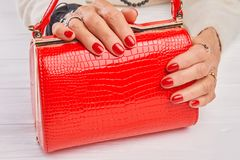 Red lacquered bag in female hands. Ol woman manicured hands with luxury jewelry holding red leather handbag. Woman luxury style royalty free stock photos