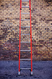 Red Ladder. Single Empty Red Ladder Leaning against a Brick Wall Stock Images
