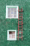 Red ladder on a green wall Stock Photo