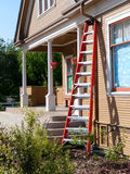 Red ladder leaning against farm house wall. Red aluminum ladder set up to fix the gutter. Victorian house with white posts Stock Image