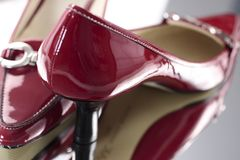 Red Ladies High Heel Shoes. Pair of dark red patent leather ladies high heeled shoes.  Red is a bright burgundy tone and heels are black.  There is a silver Royalty Free Stock Images