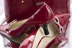 Red Ladies High Heel Shoes. Pair of dark red patent leather ladies high heeled shoes.  Red is a bright burgundy tone and heels are black.  There is a silver Stock Photo