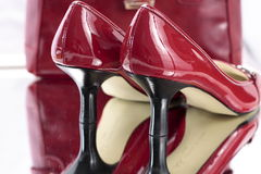 Red Ladies High Heel Shoes. Pair of dark red patent leather ladies high heeled shoes.  Red is a bright burgundy tone and heels are black.  There is a silver Stock Photos