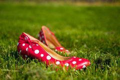 Red ladies shoes. Red speckles ladies shoes in green gras stock images
