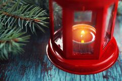 Red lantern with a burning candle inside and a Christmas tree br Stock Photography