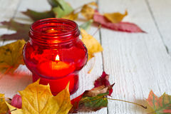 Red lantern candle with autumn leaves on white boards Royalty Free Stock Photo
