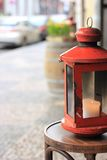 Red lantern on a chair. Old red lantern on a bentwood chair in the street Stock Photo