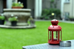 Red lantern in garden. Old fashion red lantern with lit votive on a garden table Stock Photos