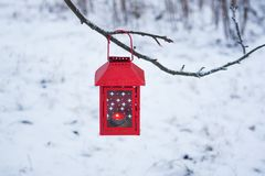 Red lantern hanging on the tree branch. Snowy winter morning in park. Red decorative lantern with candle hanging on the tree branch. Snowy winter evening in stock image