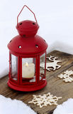 Red lantern standing on wooden board, on snow Stock Photography