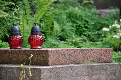 Red lantern on the tomb at the Lychakiv cemetery in Lviv. Horizontal view on two red cemetery lanterns on grave granite slab with leaves and fern at the Lychakiv Stock Image