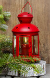 Red lantern on wooden table, under a fir branch Royalty Free Stock Image