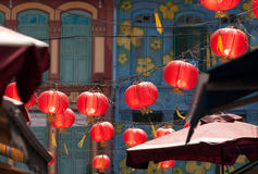 Red Lanterns in Chinatown. Red lanterns strung above the narrow lanes in Chinatown, Singapore, above the awnings of sellers selling wares to tourists Stock Photo