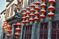 Facade of the old house decorated with red lanterns in Xidi, a small ancient village in Anhui province in China. stock photography