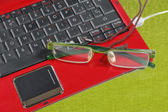 Red laptop and glasses Royalty Free Stock Photography