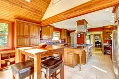 Red large luxury kitchen with wood ceiling. Stock Photos