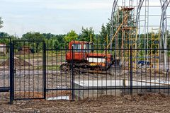 Red tractor on construction site behind a black fence. Red large tractor on construction site behind a black fence royalty free stock image