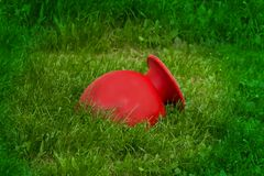 Red large vase lying in the grass royalty free stock images