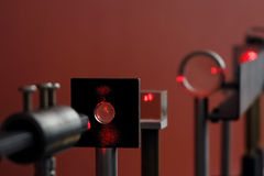 Red laser in laboratory. Red laser light passes through a series of lenses and a prism in a laboratory stock images