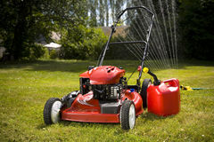 Red Lawn Mower. A red lawn mower and gas can in fresh cut grass Stock Photography