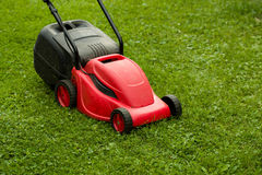 Red lawnmower on green grass Royalty Free Stock Photos