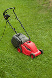 Red lawnmower on green grass Stock Photos