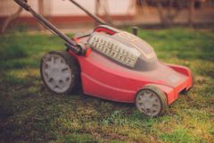 Red lawnmower on wheels stands on a trimmed lawn. In the spring yard royalty free stock photo