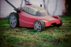 Red lawnmower on wheels stands on a trimmed lawn. In the spring yard stock images