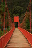 Red lead painted toll suspension footbridge. Over the Nam Song river crossing from the left-east-road bank to the Tham Jang or Chang cave on the right-west bank Royalty Free Stock Photography