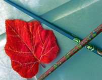 Red leaf and chopsticks. Abstract arrangement of red artificial leaf with two Oriental chopsticks Stock Photography