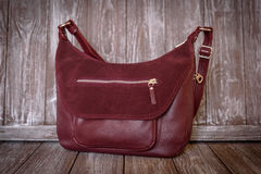Red leather bag on brown wooden background. royalty free stock photo