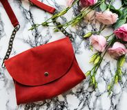 Red leather bag and flowers. On a marble background Royalty Free Stock Photography