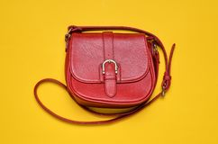 Red leather bag on a long strap on a yellow background. Women & x27;s accessories. Red leather bag on a long strap on a yellow background. Women& x27;s Royalty Free Stock Photos