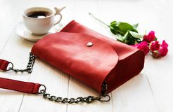 Red leather bag and flowers. Red leather bag and pink roses on a wooden background royalty free stock photography