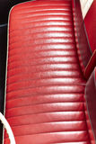 Red leather bench seats in retro  classic car. Classic  car interior. red leather bench seat with steering wheel Royalty Free Stock Images