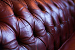 Red leather chesterfield sofa. Close-up of backrest of red buttoned chesterfield chair Stock Photos