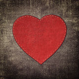 Red leather heart on fabric in grunge style Stock Photos