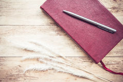 Red leather note book with pen on wood background Royalty Free Stock Photo
