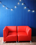 Red leather sofa on a background of blue wall with retro garland of light bulbs. Texture for the design Royalty Free Stock Image