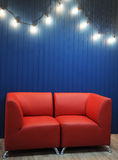Red leather sofa on a background of blue wall with retro garland of light bulbs. Texture for the design Stock Image