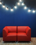 Red leather sofa on a background of blue wall with retro garland of light bulbs. Texture for the design Stock Photos