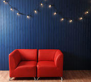 Red leather sofa on a background of blue wall with retro garland of light bulbs. Texture for the design Royalty Free Stock Images