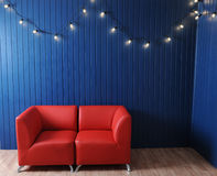 Red leather sofa on a background of blue wall with retro garland of light bulbs. Texture for the design Royalty Free Stock Photo
