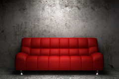 Red leather sofa in front of grunge wall Royalty Free Stock Photos