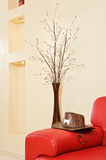 Red leather sofa headboard, hat and vase. Interior Details stock photos