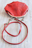 Red leather women`s handbag on wooden table Royalty Free Stock Photography